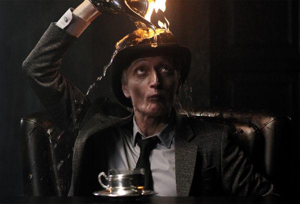 Мужчина в костюме с горящим котелком