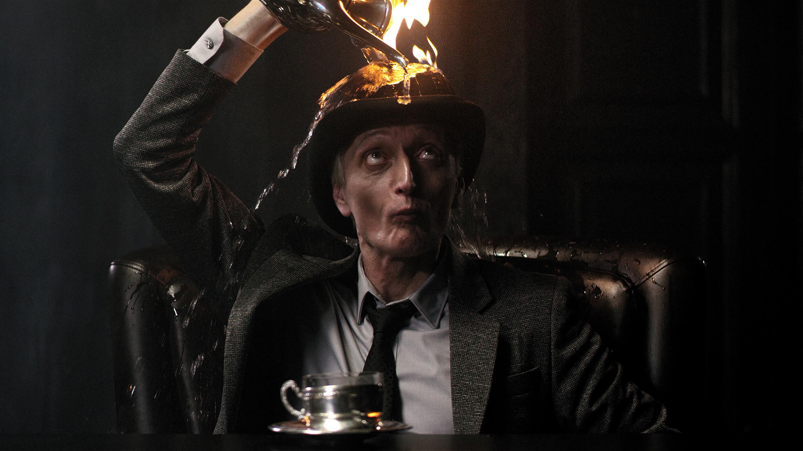 Мужчина в костюме с горящим котелком в имиджевом ролике